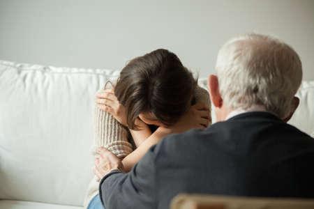 mujer llorando: Vista horizontal de abuelo consolando a su nieta llorando