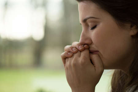 Horizontal view of depressed young woman crying Stock Photo