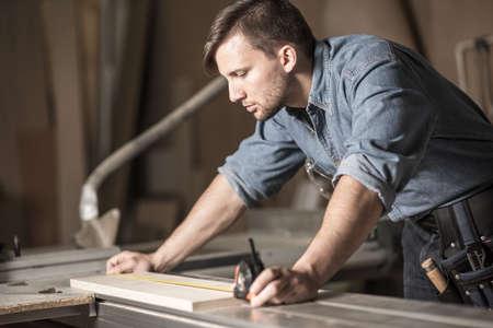 herramientas de carpinteria: Carpintero joven con cinta en el trabajo de medici�n Foto de archivo
