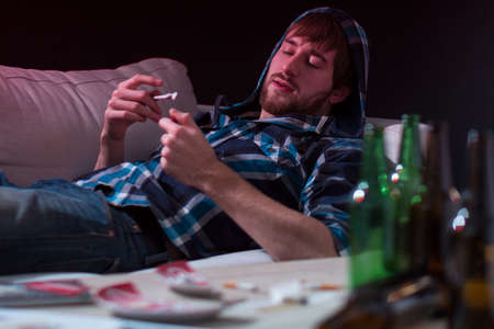 Junkie man fires a joint on the couch Stock Photo