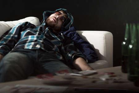 habitacion desordenada: Hombre borracho en gafas de sol para dormir en el sof�