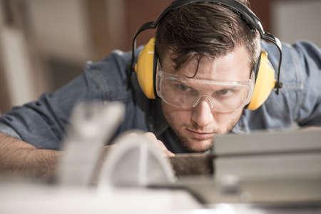travailleur: Carpenter tout en utilisant les outils �lectriques portant des �couteurs de protection Banque d'images