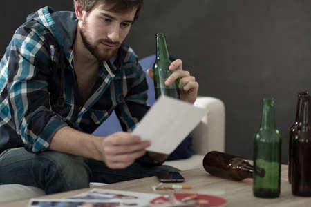 jovenes tomando alcohol: Hombre triste beber alcohol y mirando fotos