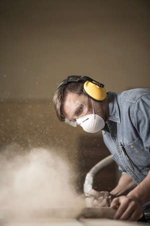 Carpenter wearing protective headphones while using electric saw Stock Photo - 41889792