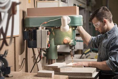 Carpenter mit Bohrmaschine in der Fabrik Standard-Bild