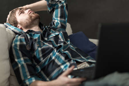 Depressed man sitting on the couch with laptop