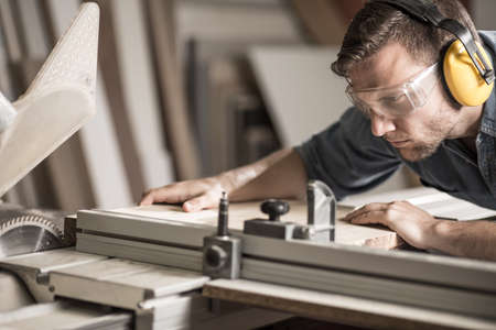 carpentry tools: Young attractive man doing woodwork in carpentry Stock Photo