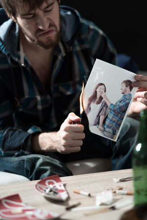 psycho: Angry man sets photo of his ex girlfriend on fire Stock Photo