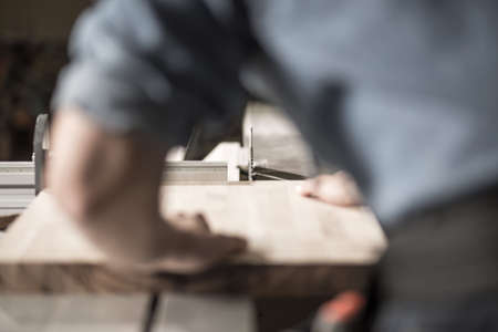 Carpenter working with a plank of wood