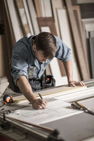 Photo of focused joiner working in carpentry