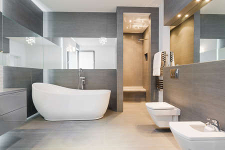 bathroom mirror: Designed freestanding bath in gray modern bathroom