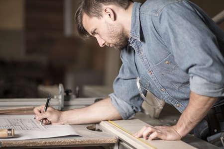 menuisier: Vue horizontale du charpentier concentré au travail