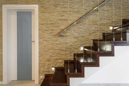 lightings: Wooden stairway and brick wall in luxury anteroom