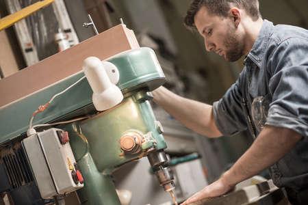 Erfahrene Carpenter mit Sägemaschine in Fabrik