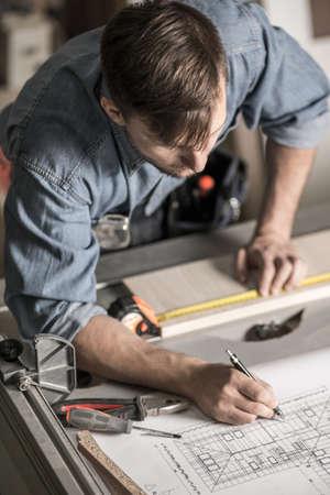 Jonge timmerman het maken van meubels tot nieuw huis