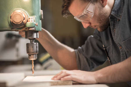 focus: Focused skilled carpenter working with drill machine