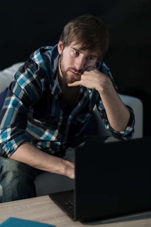 contemplated: Sad man sitting with laptop and thinking