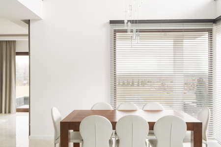 dining table and chairs: Wooden table and white chairs in dining room Stock Photo