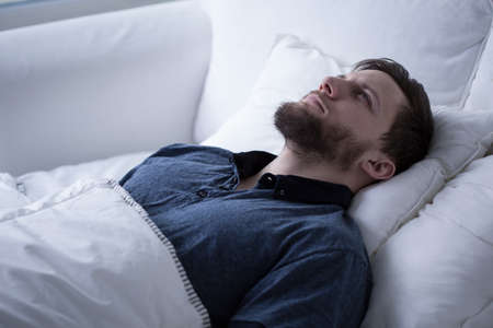 lack: Young man trying to beat insomnia promblems Stock Photo