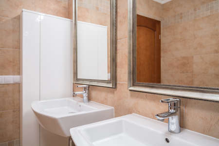 Two washbasins and mirrors in elegant beige bathroom