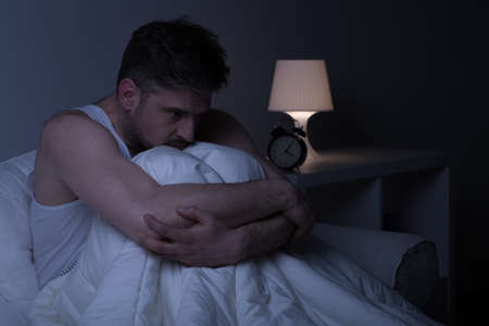 homme triste: Fatigué homme déprimé dans le lit souffrant d'insomnie