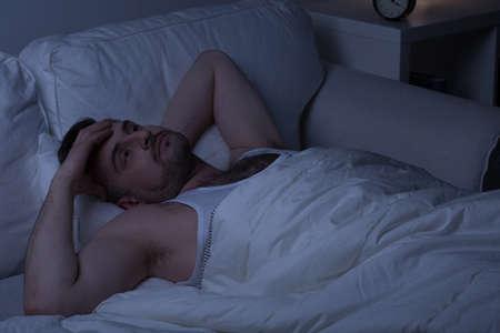 insomnio: Hombre cansado con el insomnio tratando de conciliar el sue�o