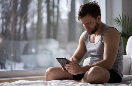 depresion: Hombre con los trastornos del sueño que utilizan dispositivos electrónicos