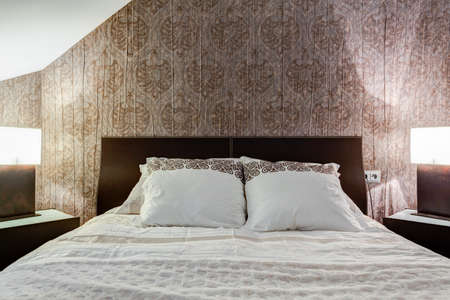 brown wallpaper: Comfortable bed and brown wallpaper in elegant bedroom