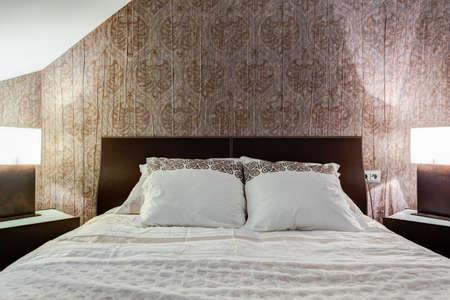 bedroom bed: Comfortable bed and brown wallpaper in elegant bedroom
