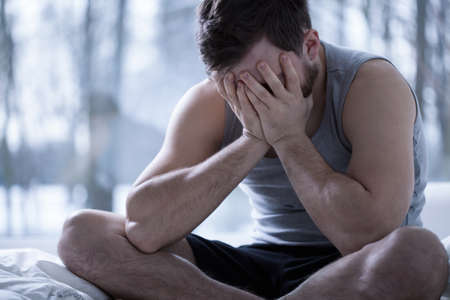 nervousness: Cross-legged sitting man suffering from insomnia Stock Photo