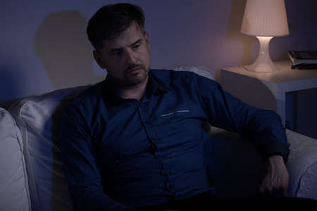 miserable: Lonely miserable man sitting in the evening at home Stock Photo