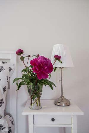 nightstand: Peony in the vase on the nightstand
