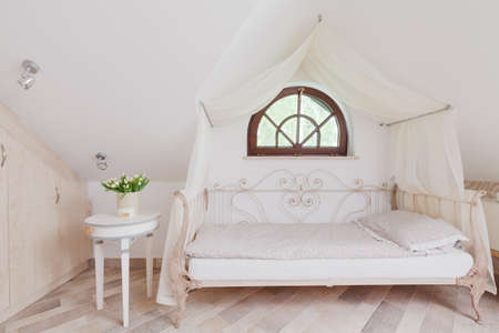 Stylish bed with canopy in romantic bedroom Stok Fotoğraf