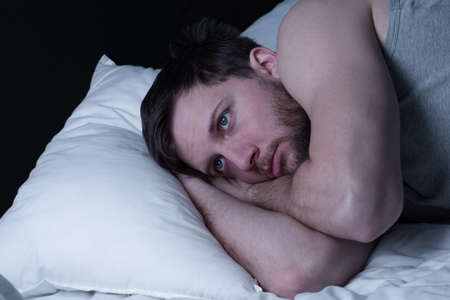 powerless: Young man having sleepless nights because of insomnia Stock Photo