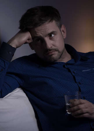miserable: Lonely miserable man drinking vodka alone at night