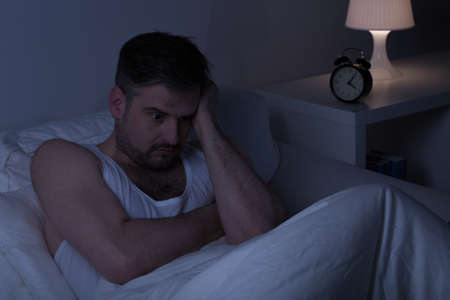 Exhausted thoughtful man in bed in early morning 版權商用圖片 - 42093798