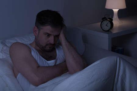 dormir: Hombre reflexivo agotado en la cama en la mañana temprano Foto de archivo