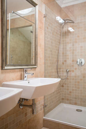 shower cubicle: Shower cubicle and washbasin in beige washroom Stock Photo
