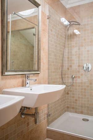 handbasin: Shower cubicle and washbasin in beige washroom Stock Photo