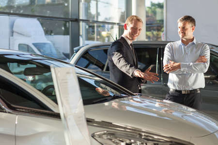 Young man working as salesman in car dealership Stock Photo