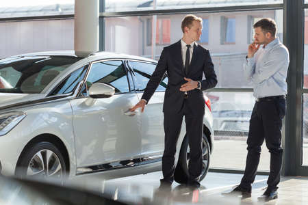 Car agent and customer in car showroom