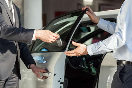 automobile dealership: Salesmans hands giving key to male customer Stock Photo