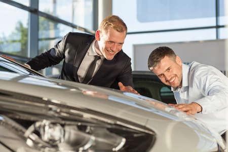 car retailer: Mature man admiring expensive vehicle in car showroom Stock Photo
