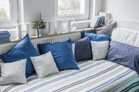 bedrooms: White and blue bedding set on the bed