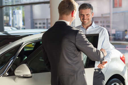 car retailer: Happy mature man buying new beauty car