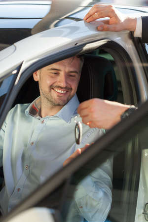 automobile dealership: Man receiving keys of his new car