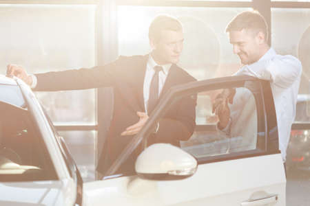 car salesperson: Handsome mature man watching vehicle in dealership