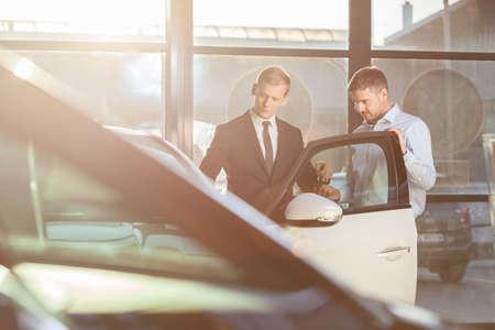 car retailer: Handsome mature businessman watching car in showroom Stock Photo