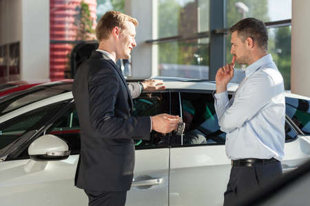 car retailer: Car agent showing vehicle to adult client
