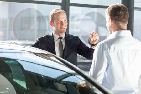 car retailer: Smiling salesman giving car key to new owner